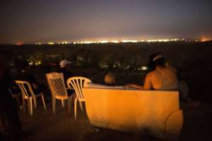 Israeli residents, mostly from the southern Israeli city of Sderot, sit on a hill overlooking the Gaza Strip, on July 12, 2014, to watch the fighting between the Israeli army and Palestinian militants. The world implored Israel and Hamas on July 12 to end hostilities as warplanes pounded Gaza for a fifth straight day, killing at least 30 Palestinians, and militants replied with rockets. AFP PHOTO / MENAHEM KAHANA (Photo credit should read MENAHEM KAHANA/AFP/Getty Images)
